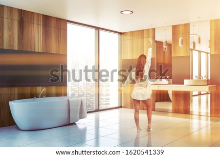Rear view of young woman standing in stylish sunlit bathroom with gray and wooden walls, tiled floor, double sink with mirrors and comfortable bathtub. Toned image #1620541339
