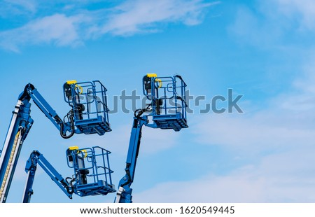 Articulated boom lift. Aerial platform lift. Telescopic boom lift against blue sky. Mobile construction crane for rent and sale. Maintenance and repair hydraulic boom lift service. Crane dealership.  #1620549445