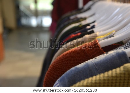 Clothes on the clothes hangers at the mall hanger are ready for sale at a discount. #1620561238