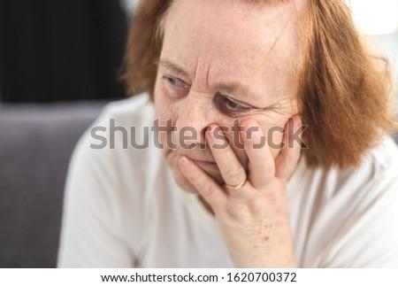 Portrait of depressed elderly woman having worries,  she worries, she thinks #1620700372