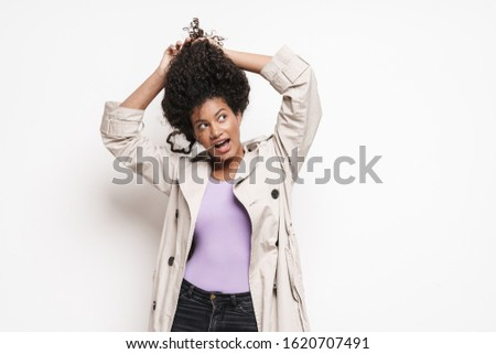 Cheerful playful attractive young african woman wearing autumn jacket having fun isolated over white background, playing with hair #1620707491