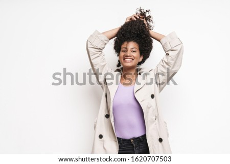 Cheerful playful attractive young african woman wearing autumn jacket having fun isolated over white background, playing with hair #1620707503