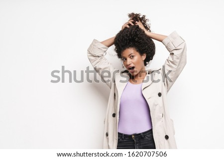 Cheerful playful attractive young african woman wearing autumn jacket having fun isolated over white background, playing with hair #1620707506