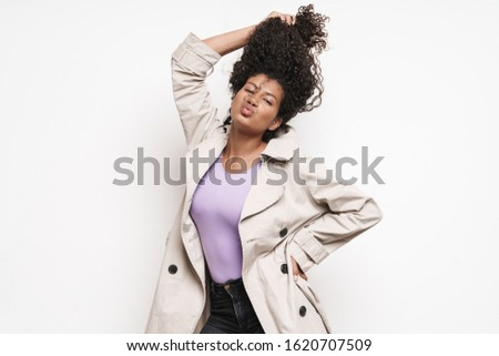 Cheerful playful attractive young african woman wearing autumn jacket having fun isolated over white background, playing with hair #1620707509