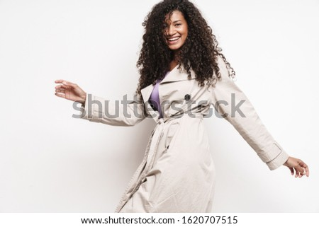 Cheerful playful attractive young african woman wearing autumn jacket having fun isolated over white background #1620707515
