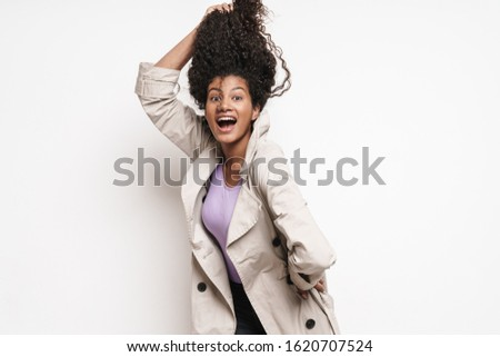 Cheerful playful attractive young african woman wearing autumn jacket having fun isolated over white background, playing with hair #1620707524