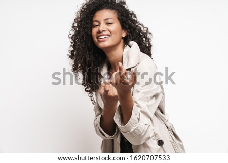 Cheerful playful attractive young african woman wearing autumn jacket having fun isolated over white background, allures #1620707533