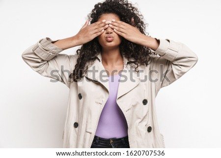 Cheerful playful attractive young african woman wearing autumn jacket having fun isolated over white background, covering face with hands #1620707536