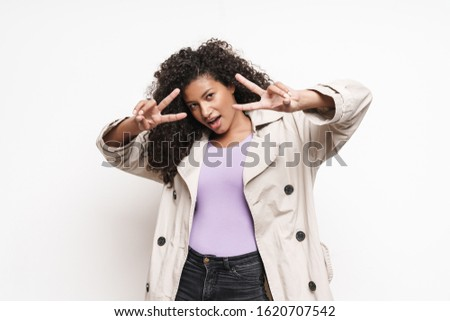Cheerful playful attractive young african woman wearing autumn jacket having fun isolated over white background, showing peace gesture #1620707542