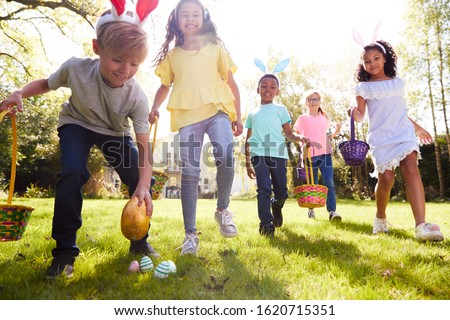 Group Of Children Wearing Bunny Ears Running To Pick Up Chocolate Egg On Easter Egg Hunt In Garden Royalty-Free Stock Photo #1620715351