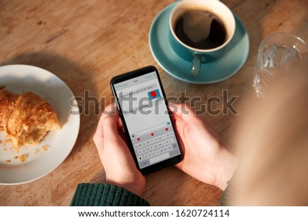 Close Up Of Woman Looking At Messages Arranging Romantic Date On Mobile Phone Messaging App In Cafe #1620724114