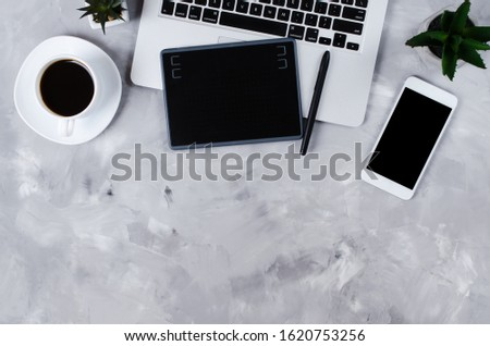 Overhead view of graphic tablet, graphic pen, smartphone, laptop and a cup of black coffee. #1620753256