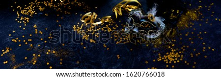 Venetian carnival mask with golden confetti and streamers on dark blue background. Horizontal decoration for traditional mardi gras with space for text and design.