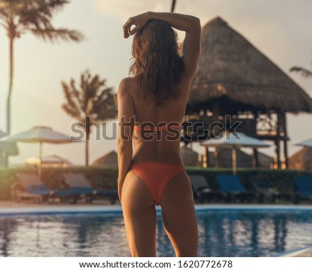 Young beautiful female model pose next to swimming pool at luxury resort in the morning #1620772678
