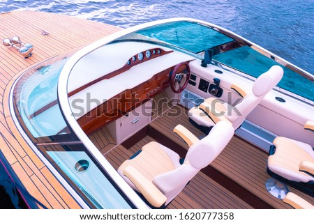 Boat top view. Travel on a pleasure boats. Fragment of a speed boat. Sale of passenger boats. Place for the control of the boat. Facing with a tree. Steering wheel. Wooden deck. Concept - luxury.  #1620777358