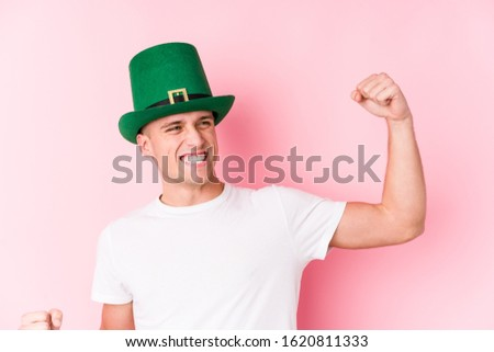 Young caucasian man celebrating saint patricks day raising fist after a victory, winner concept. #1620811333