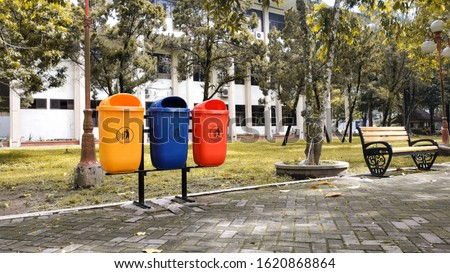 Different colored trash cans in the park. separate trash, sort waste to be recycled again. examples of modern trash cans #1620868864