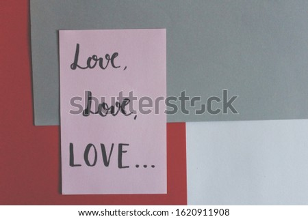 """Love love love"" handwritten on pink paper about art composition on colored papers gray and red top view #1620911908"