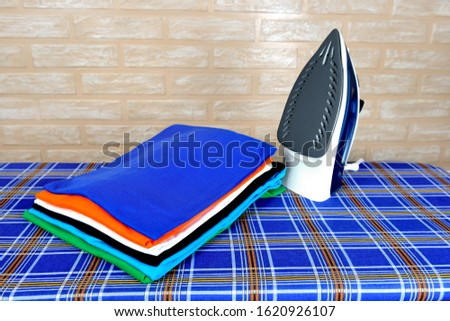New modern electric steam iron and a stack of ironed t-shirts of various colors on ironing board on a brick wall background #1620926107