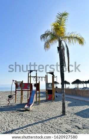 Spain the resort of Nerja. Burriana beach, the most touristic beach in Nerja. A sunny January day.  A palm tree, and slides and other childrens playthings in the late afternon sunshine. #1620927580