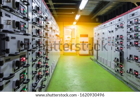 Black power supply handle Electrical selector,button at Electrical switch gear at Low Voltage motor control center cabinet in coal power plant. blurred for background.technology industry concept #1620930496