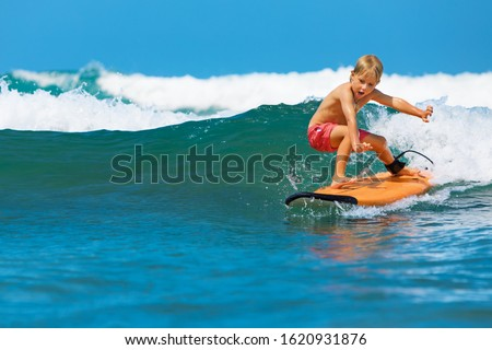 Happy baby boy - young surfer learn to ride on surfboard with fun on sea waves. Active family lifestyle, kids outdoor water sport lessons, swimming activity in surf camp. Summer vacation with child. #1620931876