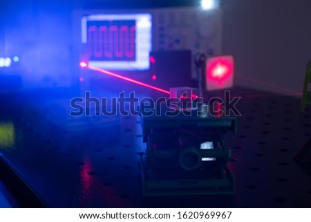 Experiment in optic lab with laser device. Red laser on optical table in physics laboratory #1620969967
