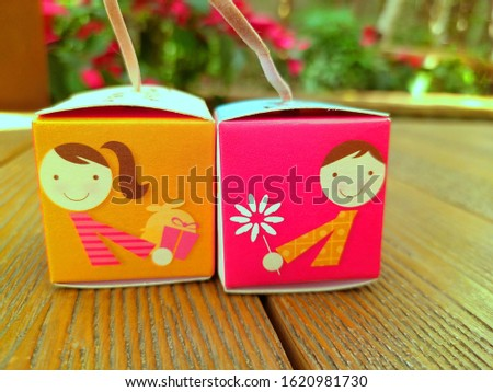 Picture of a cartoon boy on the mini paper box which he is giving a flower and picture of a cartoon girl on the another mini paper box which she is giving a present