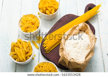 uncooked pasta variations and flour in paper bag, on white wooden table #1621013428
