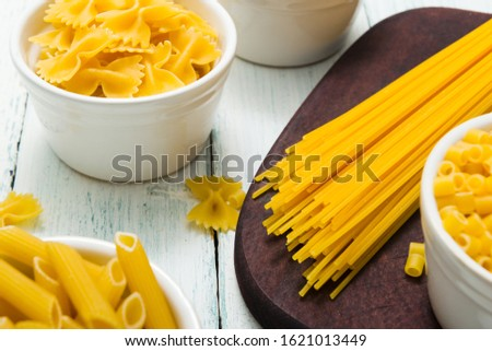 uncooked pasta variations on white wood table  #1621013449