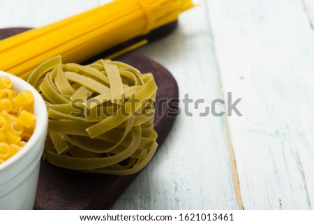 uncooked pasta variations on white wood table  #1621013461