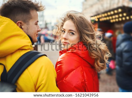 Attractive young woman in red down jacket turn around and looking in to the camera, walking with her boyfrien in city, having a date. urban romantic portrait. Romantic, love and Valentine's Day #1621043956