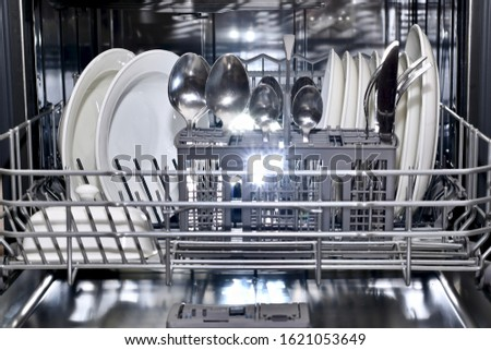 The lower shelf of the dishwasher basket is pushed forward in an orderly filled with pure sparkling utensils. #1621053649