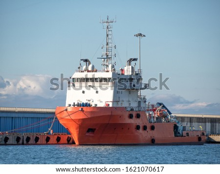 Platform supply vessel anchored in sea port at sunny day. Front view of offshore support vessel #1621070617