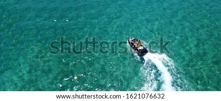 Aerial drone ultra wide photo of jet ski couple cruising in high speed in tropical exotic bay with emerald sea