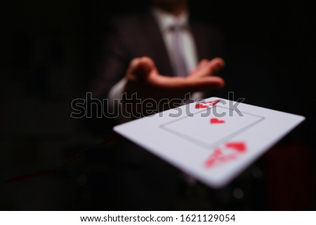 Close-up of man in presentable suit throwing playing card ace of hearts to opponent on dark background. Winning in business and risky avid player concept Royalty-Free Stock Photo #1621129054