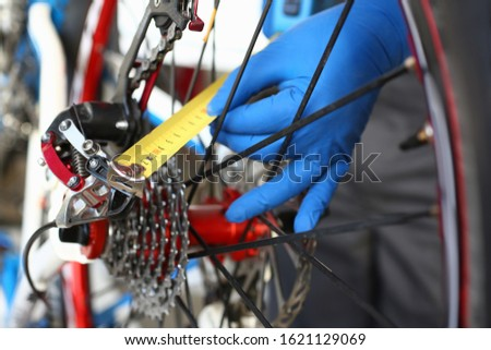 Close-up of male hands using measure tape for problem identification. Skilled mechanic working in bicycle repair shop service. Technical expertise concept #1621129069