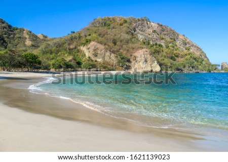 A view on an idyllic Koka Beach. Hidden gem of Flores, Indonesia. Steep slopes of the hills joining the sea. Waves gently washing the shore. There are hills in the back. Happiness and love #1621139023