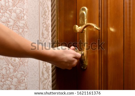 A man opens the front door by turning the handle and opening the lock. #1621161376