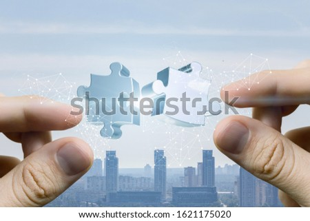 The concept Teamwork .Hands putting puzzle piece together on bright city background . #1621175020