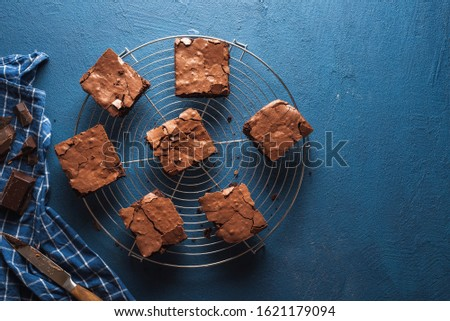 Chocolate brownies squares on a cooling tray, a blue kitchen towel, on a classic blue table. Freshly baked brownies. Best fudgy brownies cakes. #1621179094