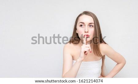 Concept of secret. Girl makes a sign shh, portrait, white background, copy space, copy space, 16:9 #1621214074