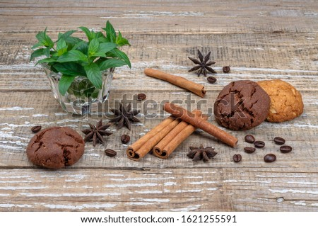 Fragrant spices and homemade cookies. Cinnamon sticks, star anise star anise and grains of coffee on a wooden background. Green leaves and stalks of mint in a glass cup.  #1621255591