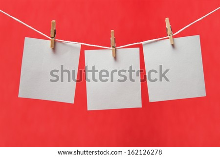 Sheets of paper on a clothespins on a red background, space for text #162126278