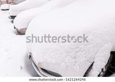 snow covered cars ofter blizzard at daylight parking - wide angle picture.