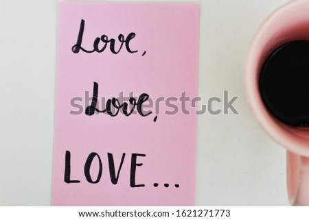 "top view of a paper with handwritten ""love love love"" lettering style, with a pink coffee mug - minimalist concept #1621271773"