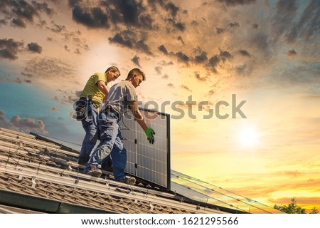 Installing solar photovoltaic panel system. Solar panel technician installing solar panels on roof. Alternative energy ecological concept.  #1621295566
