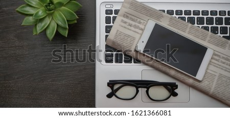 Work desk with laptop and free space for text with a lot of desk accessories. mobile cell phone with empty screen, green plant , glasses, newspaper. top view. empty copy space for inscription.