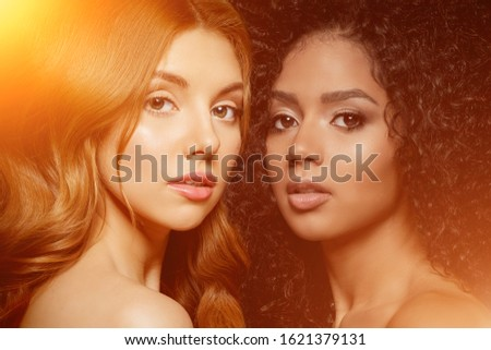 Multi-ethnic beauty. Caucasian and African. Different ethnicity women on black background. Beautiful vogue girls. #1621379131