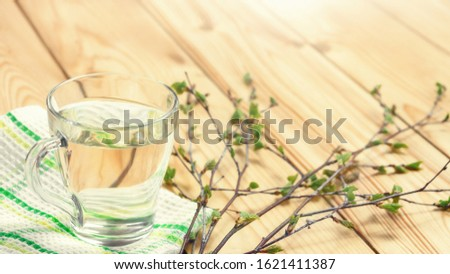 Birch juice on kitchen towel on a wooden table in a glass mug, next to a branch of birch with young leaves, horizontal banner